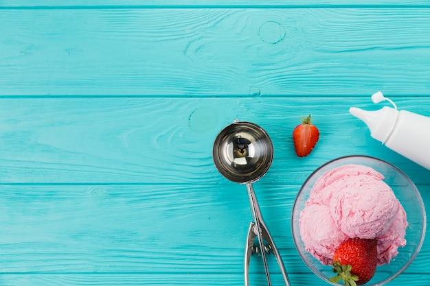 Helado de fresa y cuchara para servir.