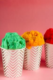 Helado de fruta verde, amarilla y roja o yogur congelado en vasos pelados
