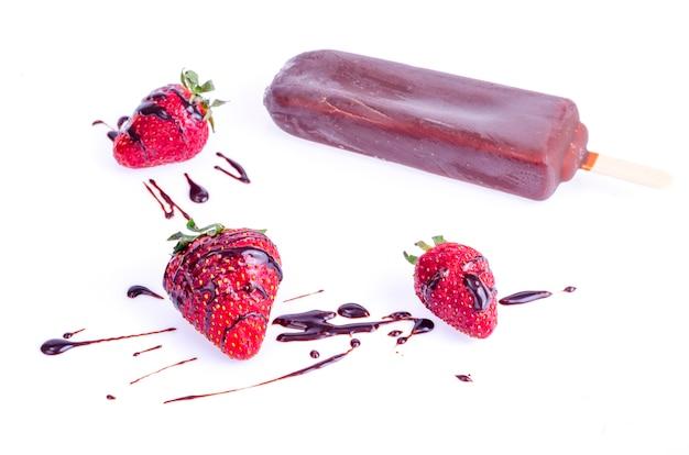 Helado en glaseado de chocolate en palito con fresas y menta
