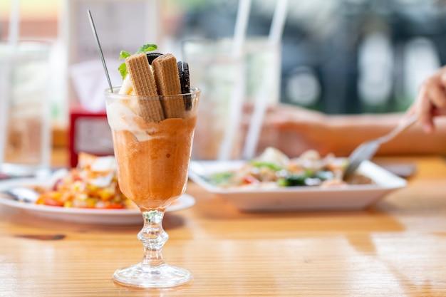 Helado de helado de vainilla con oblea en un vaso servido en un escritorio de madera en la cantina de asia
