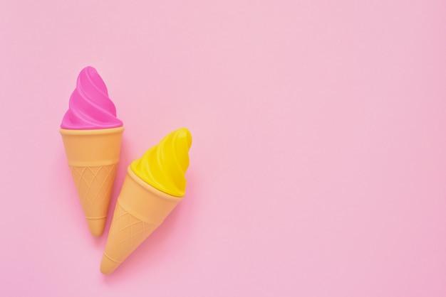 Helado de juguete rosa y amarillo sobre rosa
