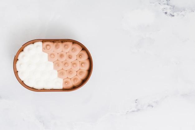 Helado mezclado en un recipiente de plástico sobre una superficie de mármol