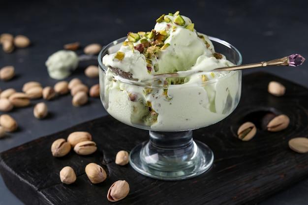 Helado de pistacho con tazón de helado de vidrio de pistachos, foto horizontal