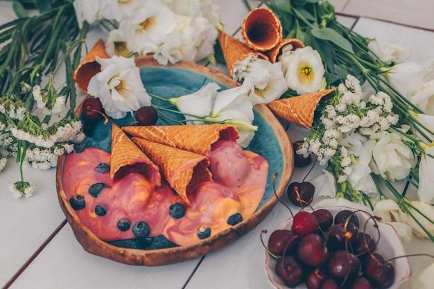 Helado en plato azul con flores y frutas en madera blanca