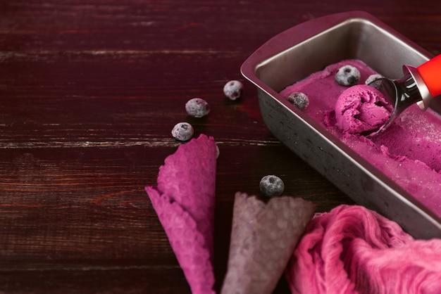 Helado rosa con una espátula para helado sobre un fondo de madera oscura con vasos de gofres