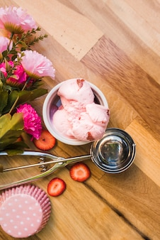 Helado rosado en un tazón cerca de la cucharada con rebanadas de bayas frescas y flores