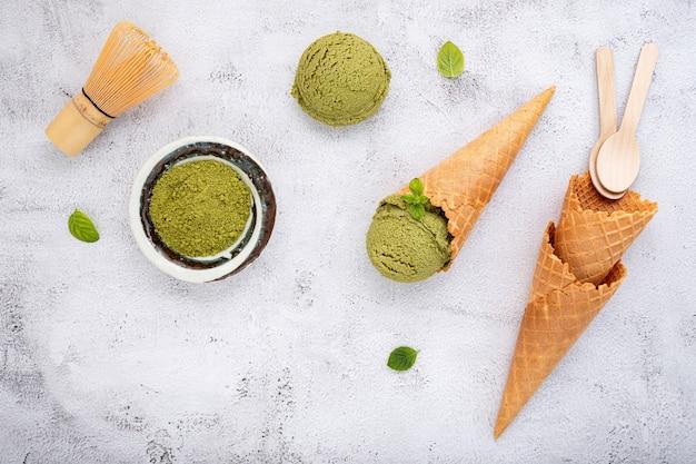 Helado de té verde matcha con cono de galleta y hojas de menta sobre fondo de piedra blanca.