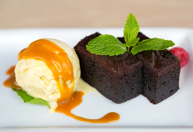 Helado de vainilla con brownies hojas de menta postre de salsa de frambuesa y caramelo