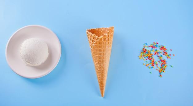 Helado de vainilla con conos de galleta y dulces sobre el fondo azul