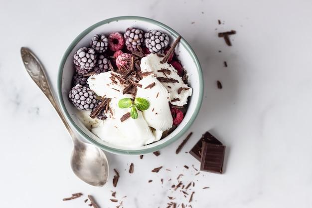 Helado de vainilla con frambuesas congeladas, moras, chocolate y menta en un tazón de cerámica.