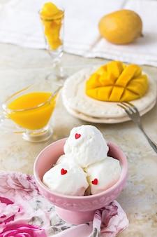 Helado de vainilla y mango. fondo claro