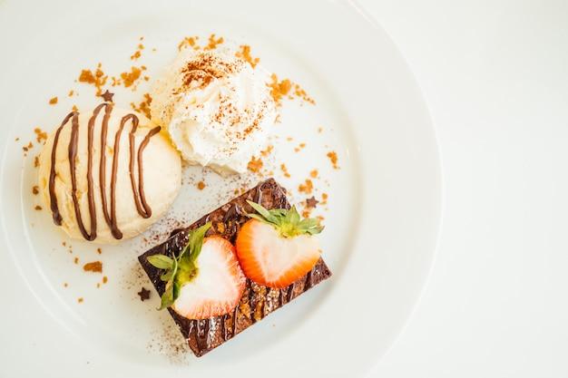 Helado de vainilla con pastel de brownie de chocolate con fresa en la parte superior