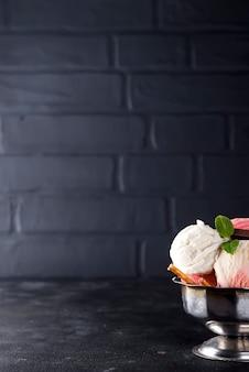 Helado de vainilla y rosa en un recipiente con bayas congeladas y cono de waffle