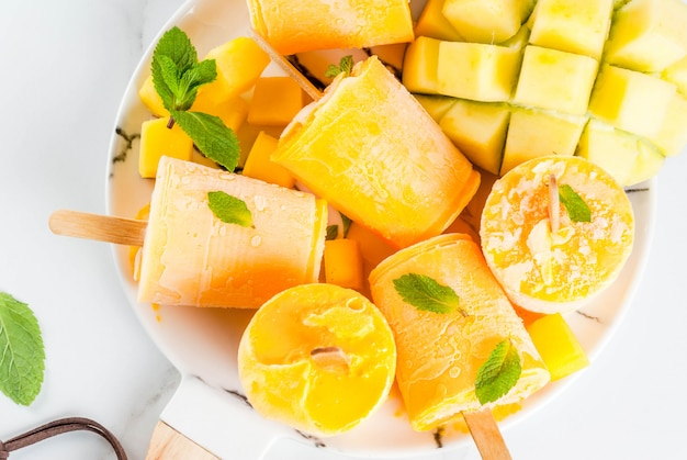 Helados, paletas de hielo. alimentos dietéticos orgánicos, postres. batido de mango congelado, con hojas de menta y fruta fresca de mango, en plato, sobre mesa de mármol blanco.