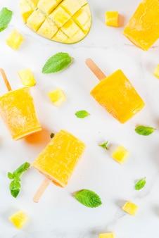 Helados, paletas de hielo. alimentos dietéticos orgánicos, postres. batido de mango congelado, con hojas de menta y fruta fresca de mango, sobre una mesa de mármol blanco. vista superior de copyspace