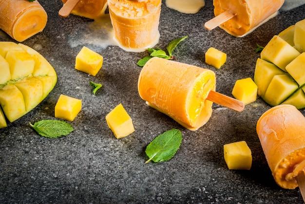 Helados, paletas de hielo. alimentos dietéticos orgánicos, postres. batido de mango congelado, con hojas de menta y fruta fresca de mango, sobre mesa de piedra negra. vista superior de copyspace