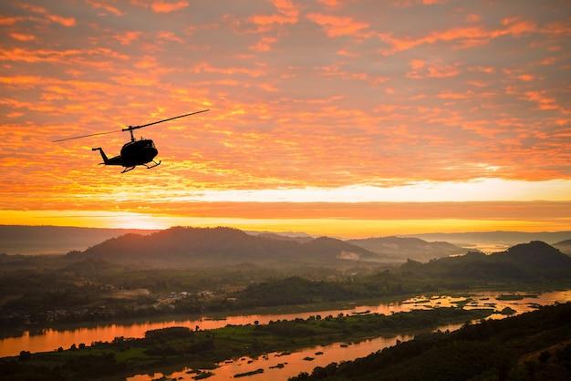 Helicóptero en puesta de sol en el río