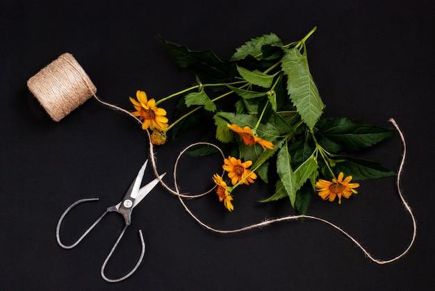 Heliopsis girasol flor con tijeras y cuerda para crear un ramo de flores sobre un fondo negro
