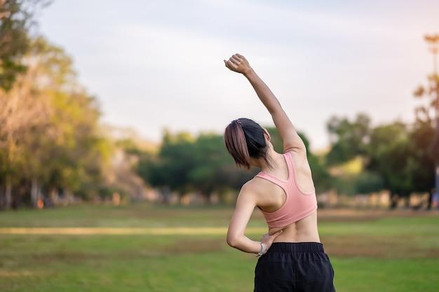 Hembra adulta joven en ropa deportiva rosa estirando los músculos en el parque al aire libre, deporte mujer calentar listo para correr y trotar en la mañana. conceptos de bienestar, fitness, ejercicio y equilibrio entre la vida laboral y personal