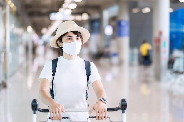 Hembra adulta joven vistiendo mascarilla en la terminal del aeropuerto