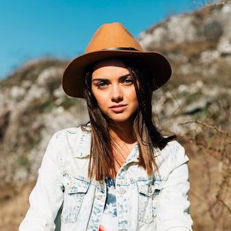 Hembra adulta sensual en sombrero en naturaleza