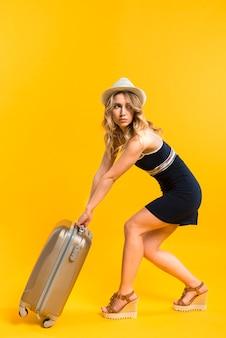 Hembra adulta en traje de verano llevando equipaje pesado