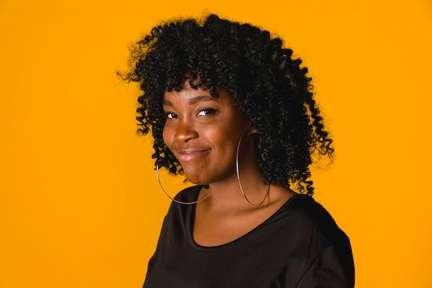 Hembra afroamericana divertida en estudio con el fondo brillante