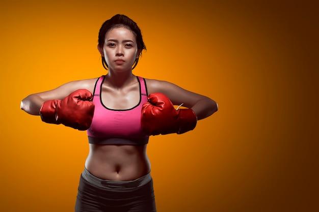 Hembra asiática deportiva del boxeador con los guantes rojos
