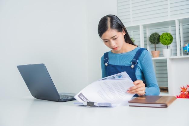 Hembra asiática joven del negocio con el trabajo financiero del papeleo serio en casa.
