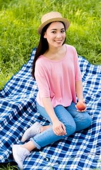 Hembra asiática con manzana sentado en tela escocesa