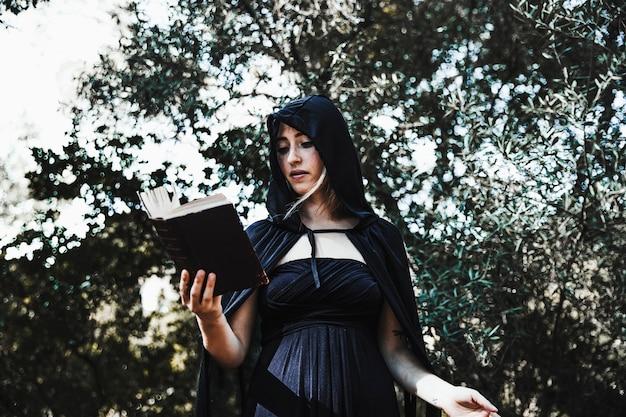 Hembra asistente con libro de hechizos en el bosque durante el día