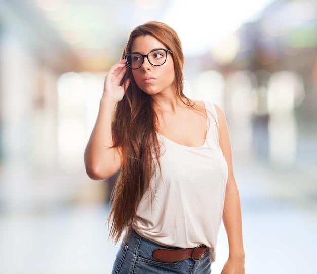 Hembra atractiva en gafas mirando a otro lado.