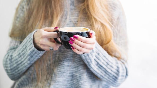Hembra de cultivo en suéter con taza de café