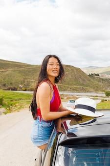 Hembra étnica joven feliz que se sienta en coche en viaje