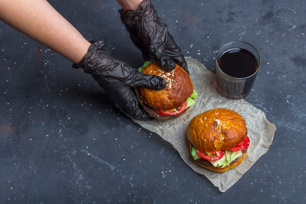 Hembra en guantes negros con hamburguesa de ternera a la parrilla recién preparada. merienda americana