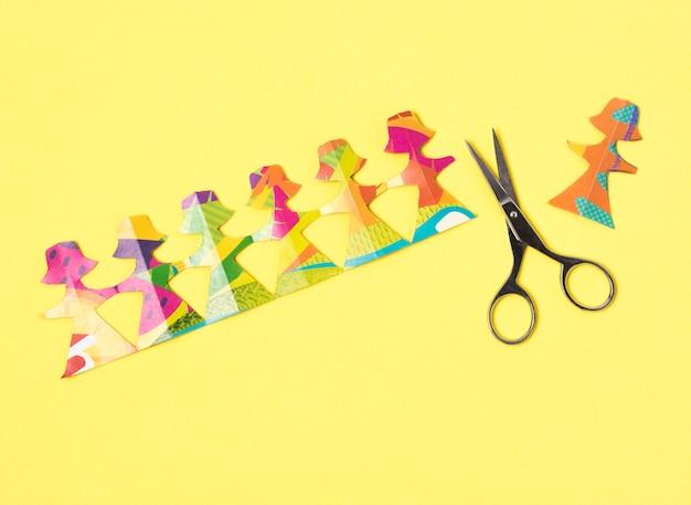Hembra hecha de papel de colores y tijeras.