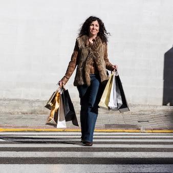 Hembra hispana caminando con bolsas de compras