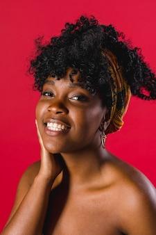 Hembra joven africana desnuda feliz en estudio