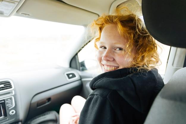 Hembra joven alegre que se sienta en coche