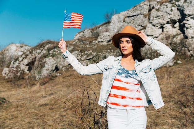 Hembra joven con bandera americana en la naturaleza.
