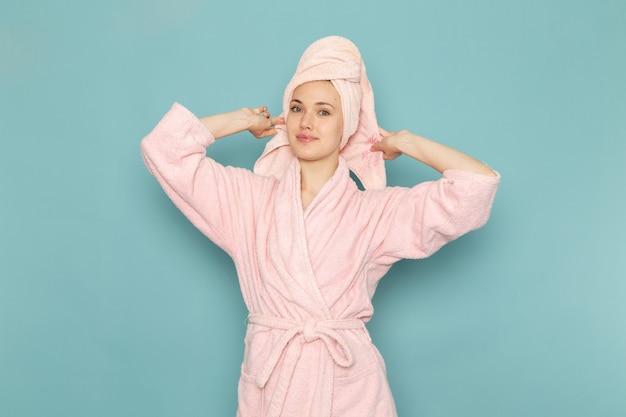 Hembra joven en bata de baño rosa después de la ducha sonriendo en azul