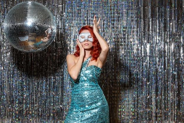 Hembra joven celebrando el año nuevo en máscara sobre cortinas brillantes