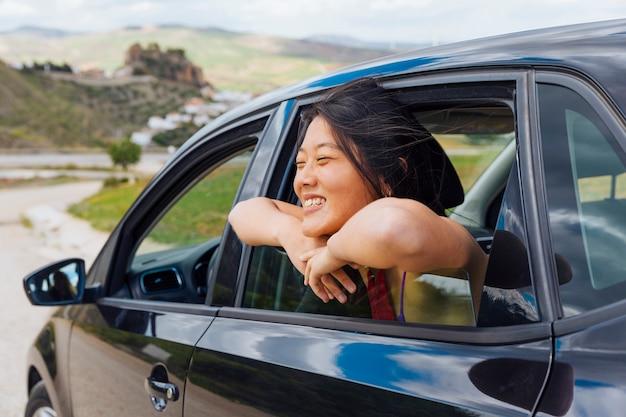 Hembra joven china alegre que mira la naturaleza de la ventana de coche