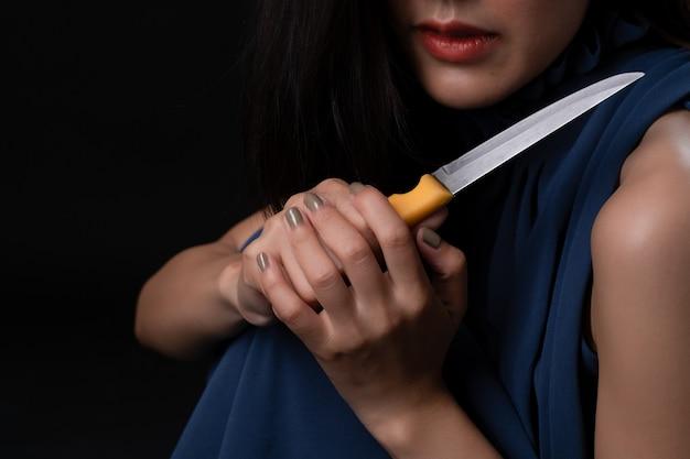 Hembra joven deprimida triste que sostiene el cuchillo disponible en oscuridad.