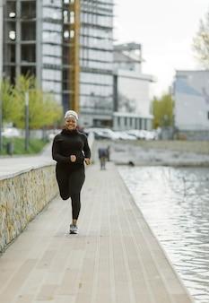 Hembra joven divirtiéndose entrenando al aire libre. concepto de estilo de vida de personas deportivas. mujer en ropa deportiva para correr