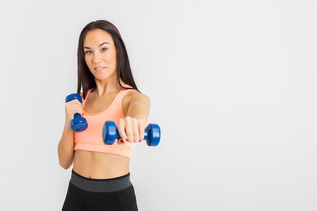 Hembra joven en el ejercicio de gimnasio con pesas