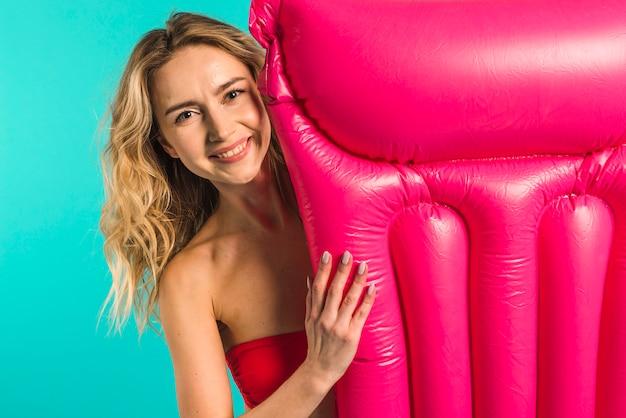 Hembra joven feliz con colchón inflable