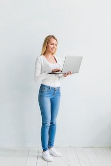 Hembra joven feliz que trabaja en la computadora portátil