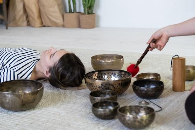 Hembra joven haciendo terapia de masaje tibetano con cuencos cantores, meditación de bienestar y bienestar