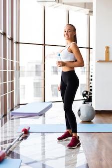 Hembra joven hidratante después de entrenar en el gimnasio